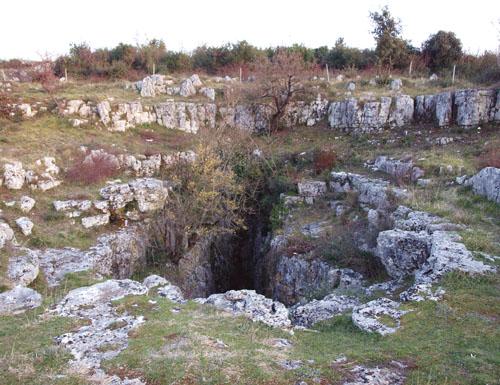 S vanjske strane sjevernog ulaza, izgrađenog od masivnih blokova, put je vodio prema okolnom predgrađu i prema jami. Ulaz u jamu je eliptičnog oblika, dimenzija 1 x 5 metara, a po vertikali se širi i spušta  do dubine od četrdeset metara, sa stepenastim nivoima. Iako je mogla služiti i kao izvor vode, smatra se da je imala obrednu namjenu, jer su oko ulaza u jamu isklesani kameni ostaci, nešto poput obrednih sjedala. Na zidovima jame nisu pronađeni crteži, no njen donji dio još uvijek nije temeljito istražen.