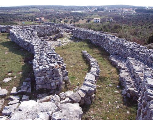 Zapadni ulaz predstavljao je glavni ulaz u grad, a iz grada je vodio prema okolnim poljima i moru udaljenom oko dva i pol kilometra. Ulaz sa stepenicama je građen u nekoliko faza i vrlo je kompleksno izveden, no tako je uzak da su kroz njega mogli proći samo ljudi ili tegleće životinje. Unutar njega, s lijeve strane, dograđene su kamene polukružne komore za koje se smatra da su služile kao mjesto ukopa i bile povezane s kultom predaka.