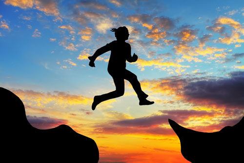 Woman jump over canyon