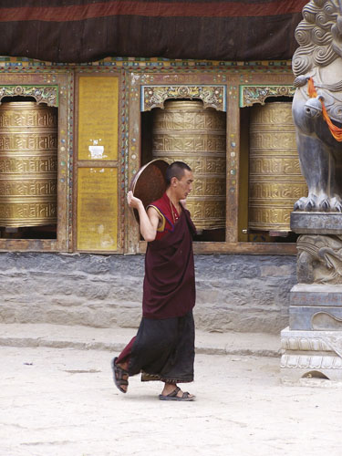 Monk with pan by prayer wheels, Sakya Monastery, Tibet