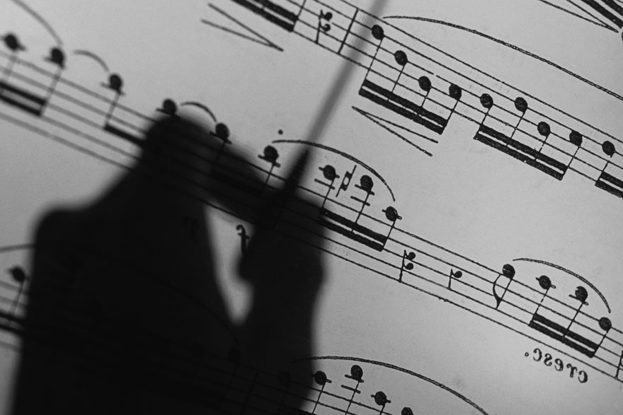 Silhouette of a hand conducting over sheet music