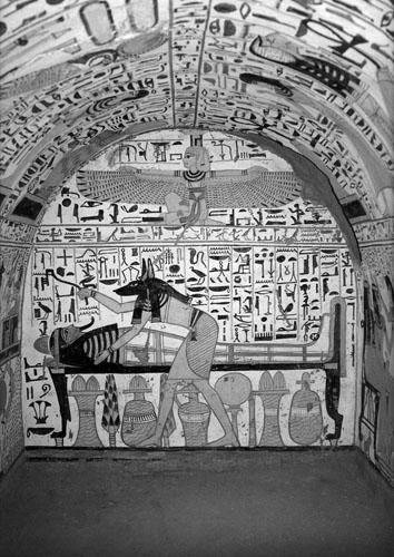 """Bog Anubis naginje se nad mumijom, držeći u ruci metalni predmet od meteoritskog željeza koji se koristio za obred """"otvaranja usta umrlog"""". Grobnica Nebenmaat, Teba, XX. dinastija."""