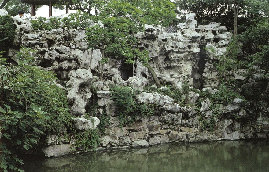 """Dio stjenjaka iz vrta Shi Zi Lin u Suzhou. Ovaj je vrt u potpunosti preuređen u XVI. stoljeću i danas se u njemu nalazi najveća """"umjetna planina"""" u Suzhou. Unutar ove stjenovite strukture nalazi se labirint malih špilja, usjeka i hodnika koji vijugaju kroz stijenu, dok su na površini stijene neobičnih oblika koje podsjećaju na različite životinje, lica i figure."""